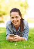 Uśmiechnięta młoda dziewczyna z smartphone lying on the beach na trawie Zdjęcia Royalty Free