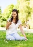 Uśmiechnięta młoda dziewczyna z smartphone obsiadaniem w parku Fotografia Royalty Free