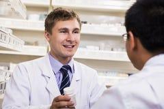 Uśmiechnięta młoda farmaceuta pokazuje recepturowego lekarstwo klient fotografia royalty free