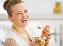 Uśmiechnięta młoda gospodyni domowej łasowania owoc sałatka Zdjęcie Stock