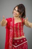 Uśmiechnięta młoda Indiańska kobieta pokazuje kciuk up podpisuje z oba rękami Obrazy Stock