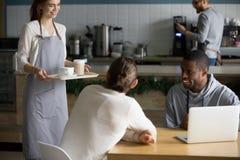 Uśmiechnięta młoda kelnerka serw kawa męscy cukierniani goście obraz royalty free