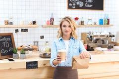 uśmiechnięta młoda kelnerki mienia kawa iść w papierowej filiżance i brać oddalonego jedzenie Zdjęcie Stock