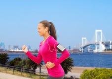Uśmiechnięta młoda kobieta biega outdoors Fotografia Stock