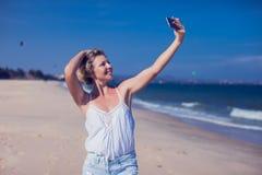 Uśmiechnięta młoda kobieta bierze selfie fotografię przy piaskowatą plażą se obrazy royalty free