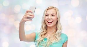 Uśmiechnięta młoda kobieta bierze selfie z smartphone Fotografia Stock