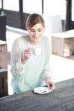 Uśmiechnięta młoda kobieta cieszy się filiżankę kawy przewyższa Fotografia Royalty Free