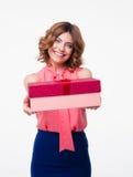 Uśmiechnięta młoda kobieta daje prezenta pudełku na kamerze Zdjęcie Stock