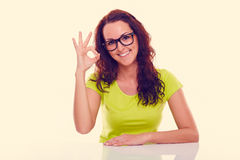 Uśmiechnięta młoda kobieta gestykuluje ok stonowany obraz royalty free
