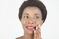 Uśmiechnięta młoda kobieta muska jej twarz zdjęcia royalty free