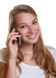 Uśmiechnięta młoda kobieta na smartphone fotografia royalty free