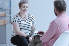 Uśmiechnięta młoda kobieta opowiada doradca o bu z tatuażami zdjęcia royalty free