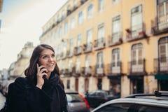 Uśmiechnięta młoda kobieta opowiada na jej smartphone na ulicie Komunikujący z przyjaciółmi, uwalnia wezwania i wiadomości dla mł fotografia royalty free