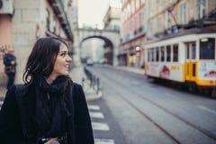 Uśmiechnięta młoda kobieta opowiada na jej smartphone na ulicie Komunikujący z przyjaciółmi, uwalnia wezwania i wiadomości dla mł obraz royalty free