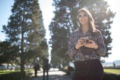 Uśmiechnięta młoda kobieta opowiada na jej smartphone na ulicie Komunikujący z przyjaciółmi, uwalnia wezwania i wiadomości dla mł zdjęcie stock