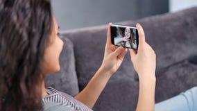 Uśmiechnięta młoda kobieta opowiada na wideo gadka związku z dziewczyna przyjacielem używa smartphone w górę zbiory