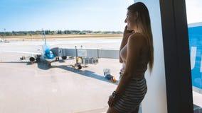 Uśmiechnięta młoda kobieta opowiada telefonem komórkowym przy lotniskowym i patrzeje na samolotach na pasie startowym fotografia royalty free