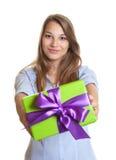 Uśmiechnięta młoda kobieta pokazuje boże narodzenie prezent zdjęcie stock