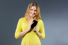 Uśmiechnięta młoda kobieta pokazuje mądrze telefon fotografia royalty free