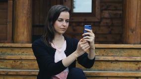 Uśmiechnięta młoda kobieta pozuje brać selfie outdoors zbiory wideo