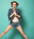 Uśmiechnięta młoda kobieta skacze w ai z mikrofonem i hełmofonami Zdjęcia Stock