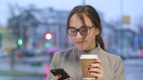 Uśmiechnięta młoda kobieta sprawdza ogólnospołecznych środki na jej smartphone podczas gdy pijący kawę zdjęcie wideo