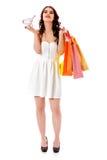 Uśmiechnięta młoda kobieta trzyma małego pustego wózek na zakupy i torba na zakupy fotografia royalty free
