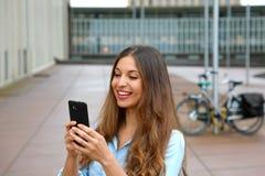 Uśmiechnięta młoda kobieta używa app w jej smartphone przyrządzie wysyłać wiadomość tekstową podczas gdy stojący w podwórzu biuro fotografia stock