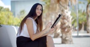 Uśmiechnięta młoda kobieta używa jej pastylkę outdoors zbiory