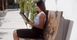 Uśmiechnięta młoda kobieta używa jej pastylkę outdoors zdjęcie wideo