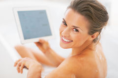 Uśmiechnięta młoda kobieta używa pastylka komputer osobistego w wannie. tylni widok Obraz Stock