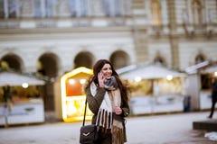 Uśmiechnięta młoda kobieta używa telefon na ulicie przy zimnym zima dniem obraz royalty free