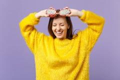 Uśmiechnięta młoda kobieta utrzymuje oczy w futerkowym pulowerze zamykał mień halfs pitahaya, smok owoc odizolowywająca na fiołko fotografia royalty free