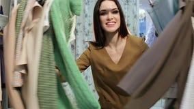 Uśmiechnięta młoda kobieta wśród stojaków odziewa Szczęśliwa Shopaholic kobieta zbiory wideo