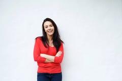 Uśmiechnięta młoda kobieta w czerwony koszulowy ono uśmiecha się przeciw białemu tłu Obraz Stock
