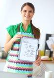 Uśmiechnięta młoda kobieta w kuchni, odizolowywającej dalej Zdjęcie Royalty Free