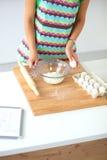 Uśmiechnięta młoda kobieta w kuchni, odizolowywającej dalej Zdjęcia Royalty Free