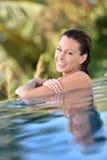 Uśmiechnięta młoda kobieta w pływackim basenie ma zabawę Fotografia Stock