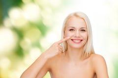 Uśmiechnięta młoda kobieta wskazuje jej nos Zdjęcia Royalty Free