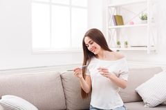Uśmiechnięta młoda kobieta z ciążowego testa obsiadaniem na kanapie obrazy stock