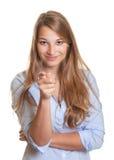 Uśmiechnięta młoda kobieta z długi blondynu wskazywać  fotografia royalty free