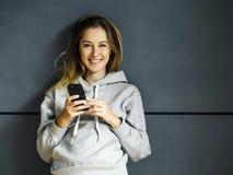 Uśmiechnięta młoda kobieta z jej telefonem komórkowym zdjęcia royalty free