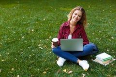 Uśmiechnięta młoda kobieta z laptopem outdoors obrazy stock