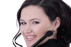 Uśmiechnięta młoda kobieta z muśnięciem dla makeup zdjęcia stock
