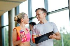 Uśmiechnięta młoda kobieta z osobistym trenerem w gym Obrazy Stock