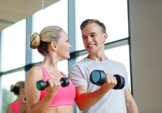 Uśmiechnięta młoda kobieta z osobistym trenerem w gym Zdjęcie Royalty Free