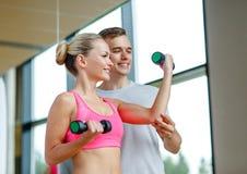 Uśmiechnięta młoda kobieta z osobistym trenerem w gym Obrazy Royalty Free