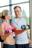 Uśmiechnięta młoda kobieta z osobistym trenerem w gym Obraz Stock