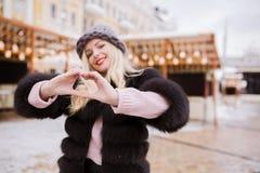 Uśmiechnięta młoda kobieta z sercem kształtującym wręcza pozować na backgriu Zdjęcie Royalty Free