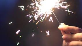 Uśmiechnięta młoda kobieta z sparkler przy zmierzchem w zwolnionym tempie zbiory